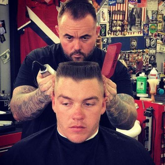 Homem na barbearia com o barbeiro atrás dele executando o corte. Seu cabelo está bem raspado nas lateral e o topo tem os fios mais longos, penteados para cima em forma quadrangular.