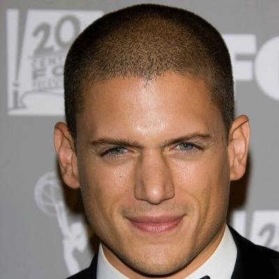 Homem de terno sorrindo para a câmera. Seu cabelo é raspado na mesma altura em toda a dimensão da cabeça.