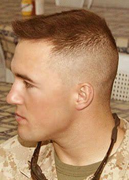 Homem de perfil com corte de cabelo militar. Ele usa um topete pequeno com um leve degradê na lateral.