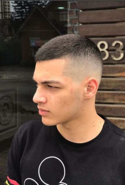 Foto de um homem com cabelo curto no topo e raspado na lateral com degradê.
