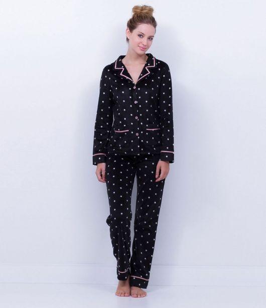 Modelo usa pijama preto com bolinha branca de botão.