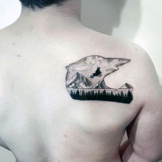 Tatuagem nas costas de um homem com o formato de um capacete e dentro dele uma paisagem onde um motoqueiro está pulando alto com sua moto.