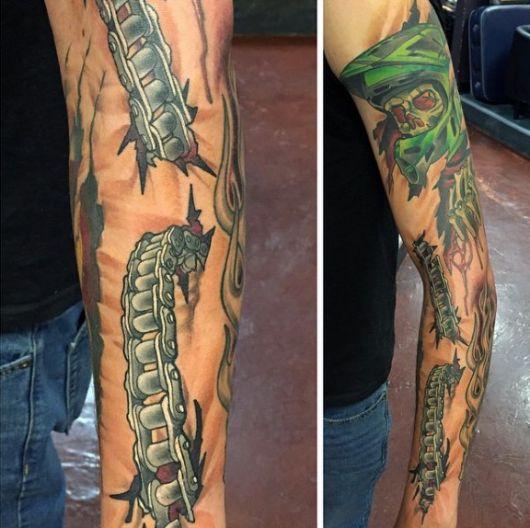 Tatuagem biomecânica  fechando o braço de um homem. Há uma corrente que parece entrar em um ponto da pele e sair mais abaixo.