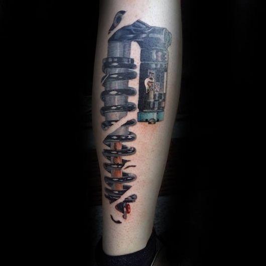 Tatuagem biomecânica na canela com o desenho de uma mola parcialmente coberta pela pele.