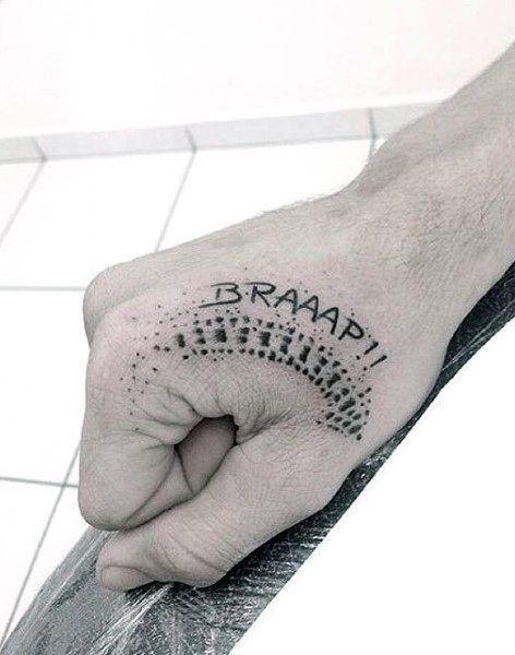 """Tatuagem na mão de um homem com o desenho da freada de uma moto e acima dele a expressão """"Braaap!!"""" escrita."""