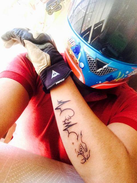 Tatuagem no antebraço de um homem com luva e capacete. A tatuagem começa com sinais de batimentos cardíacos e vai se transformando em uma moto.