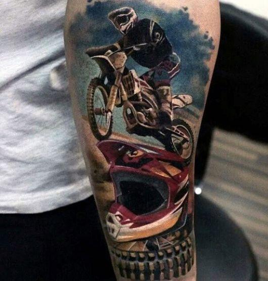 Tatuagem de um atleta de motocross pilotando sua moto com o céu azul ao fundo e um capacete no chão em primeiro plano.