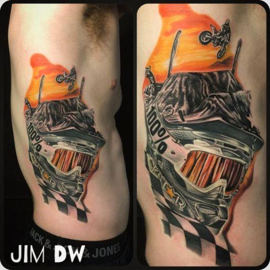 Tatuagem na costela de um homem com o desenho de um capacete colorido em primeiro plano e no fundo um atleta de motocross saltando em obstáculos naturais.