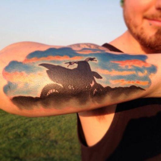 Tatuagem na parte externa do antebraço de um homem com o desenho da silhueta de uma moto e o céu colorido ao fundo.
