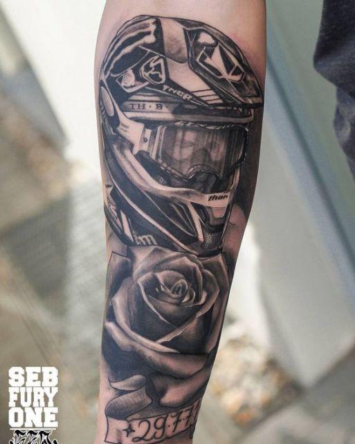 Tatuagem de motocross realista feita no antebraço com o desenho de um atleta de motocross vestindo um capacete e um óculos de proteção. Abaixo dele há uma rosa.