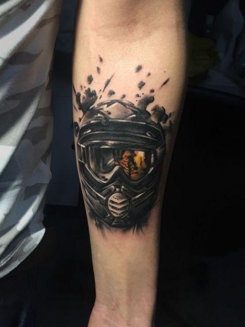 Tatuagem de motocross realista com o desenho de um atleta de motocross vestindo o óculos e o capacete. No reflexo do óculos há uma floresta pegando fogo.