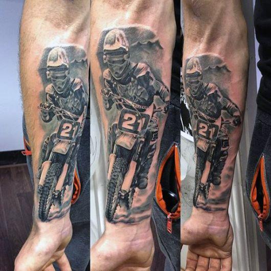 Tatuagem de motocross realista feita no antebraço com o desenho de um atleta de motocross dirigindo sua moto em uma estrada.