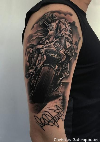 Tatuagem de motocross realista feita na parte de cima do braço de um homem. O desenho parece uma fotografia tirada pelas costas de um atleta de motocross uniformizado em sua moto .
