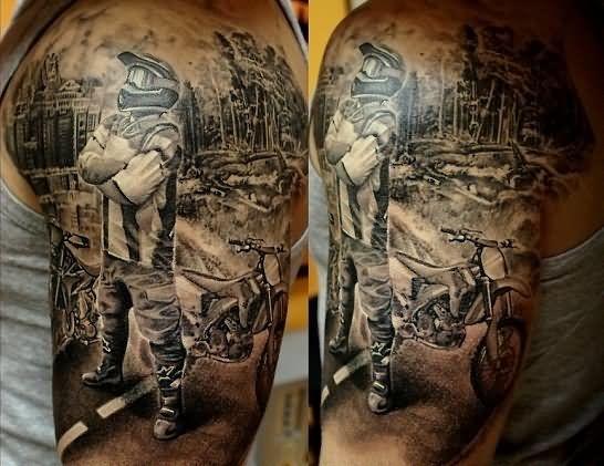 Tatuagem de motocross realista na parte superior do braço de um homem. Ele está de pé com os braços cruzados em frente à sua moto e ao fundo há a paisagem de uma cidade.