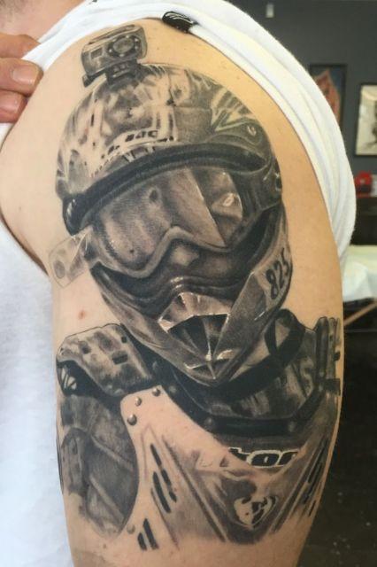 Tatuagem de motocross realista com o desenho de um atleta de motocross vestindo óculos de proteção e capacete. No topo do capacete há um máquina Go Pro.