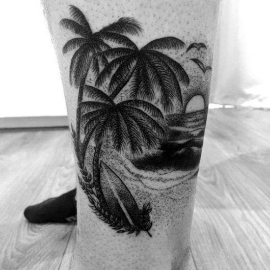 Tatuagem na perna de um homem com uma bela paisagem. Nela vemos três coqueiros, uma prancha encostada neles e o mar à frente com sol saindo dele.