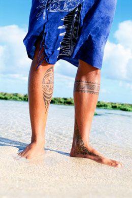 Homem de canga pisando na areia em frente ao mar com tatuagens maori nas duas pernas.