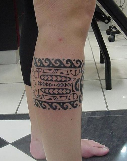 Tatuagem maori na perna de um homem com desenhos que lembram pranchas de surf.