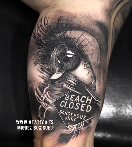 Tatuagem na parte interna do braço com o desenho de um olho e um surfista saindo dele indo em direção ao mar.