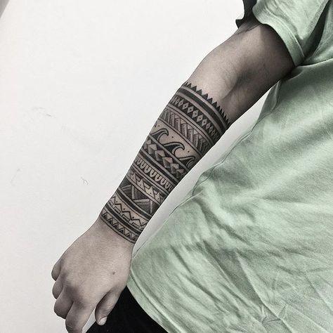Homem com tatuagem maori cobrindo todo seu antebraço. Algumas formas da tatuagem formam ondas.