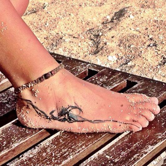 Tatuagem que vai do calcanhar ao dedo mindinho de uma mulher com o desenho do mar e uma onda grande no meio dele. A mulher está sentada na praia e tem seu pé coberto com grãos de areia.