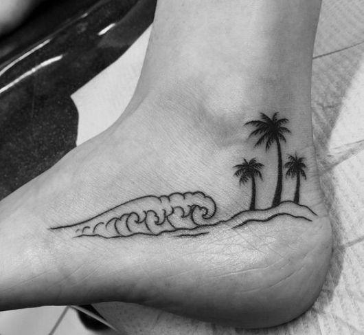 Tatuagem próxima ao calcanhar de uma mulher com o desenho de ondas no mar indo direção a uma pequena praia com três coqueiros.