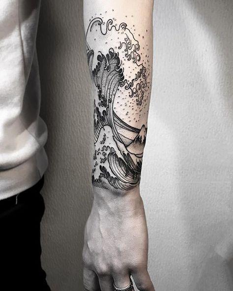 Tatuagem cobrindo 360º do braço de um homem com o desenho do mar e altas ondas se formando.