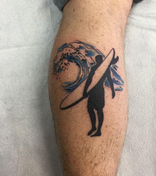 Tatuagem na panturrilha de um homem com a silhueta de um surfista segurando uma prancha enquanto caminha em direção ao mar.