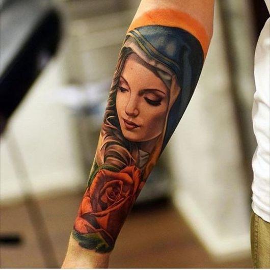 Tatuagem colorida na parte interna do antebraço de uma mulher com o desenho de uma versão angelical da Virgem Maria acompanhada de uma rosa.
