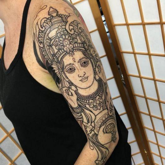 Tatuagem cobrindo toda a parte interna superior do braço de uma mulher com o desenho do rosto da Deusa Lakshmi repleta de adornos.