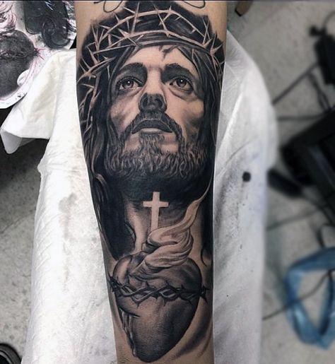 Tatuagem no braço de uma mulher com o rosto de Jesus olhando para cima com um coração sacro abaixo dele.