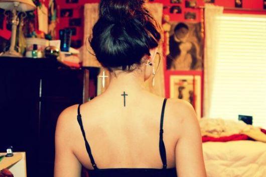 Tatuagem das costas de uma mulher com uma cruz delicada simples no centro.