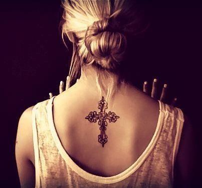 Tatuagem das costas de uma mulher com a tatuagem de uma cruz adornada com rosas no centro.