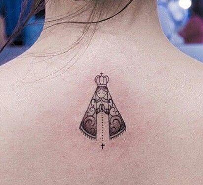 Tatuagem pequena nas costas de uma mulher com o desenho minimalista da Virgem Maria rezando.
