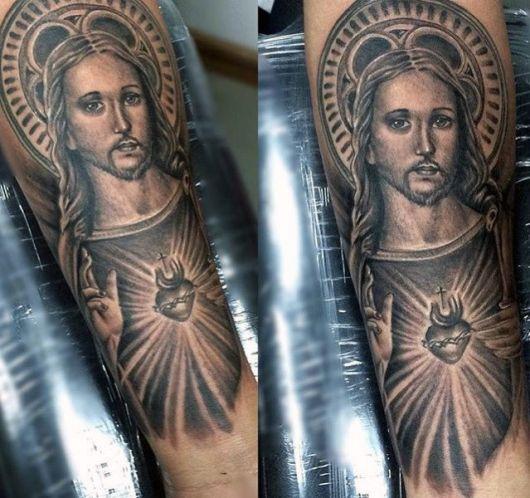 Tatuagem em tons de cinza de Jesus com as mãos aberta e um coração sacro em seu peito.