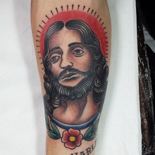 Tatuagem em estilo tradicional do rosto de Jesus com um sol em cores vivas atrás de sua cabeça.
