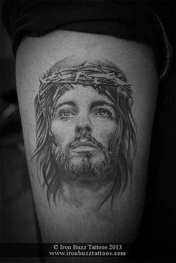 Tatuagem do rosto de Jesus em estilo realista. Ele está olhando para o horizonte e usa a coroa de espinhos.
