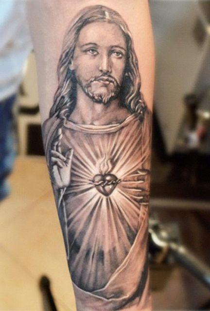 Tatuagem de Jesus no braço de uma mulher com o desenho de Jesus em estilo realista de mãos abertas e um coração sacro em seu peito.