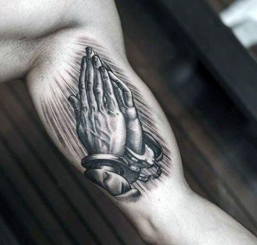 Tatuagem na parte interno do braço de um homem com o desenho de duas mãos algemadas rezando.