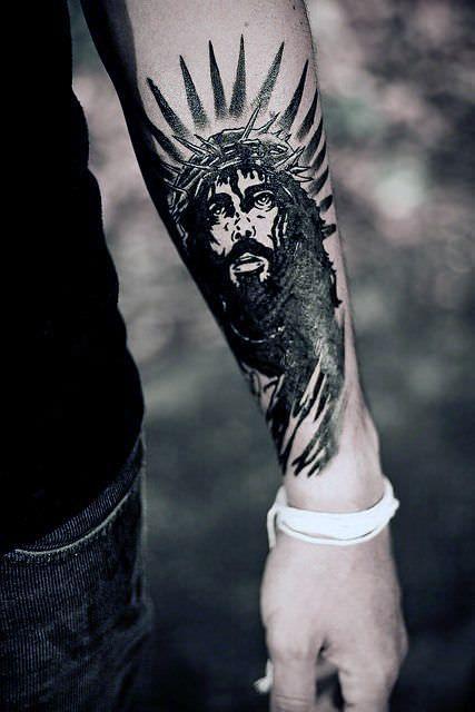 Tatuagem do rosto de Jesus no antebraço de um homem. Jesus é pintado em tons escuros e tem expressão de dor com a coroa de espinhos em sua cabeça.