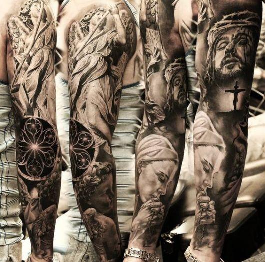 Tatuagem fechando o braço de um homem com desenhos do rosto de Jesus, da Virgem Maria e de outros anjos.