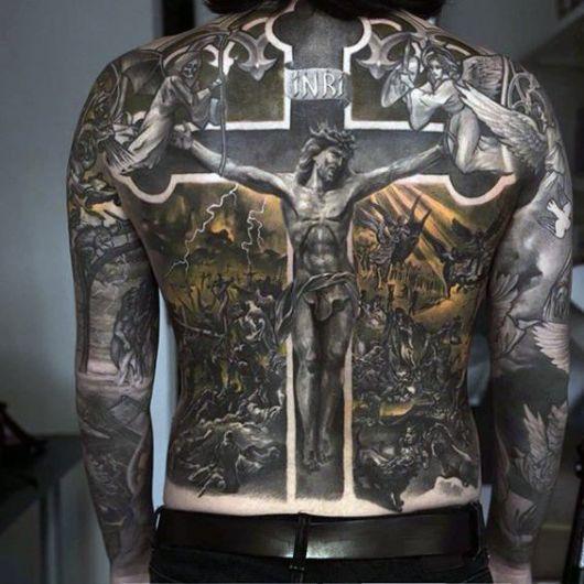 """Tatuagem cobrindo as costas de um homem com o desenho com a cena de uma guerra bíblica e no centro Jesus colocado em uma cruz com a placa """"Inri"""" nela."""