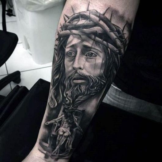 Tatuagem no braço de um homem com o rosto de Jesus e abaixo uma imagem dele sentado em uma cadeira cabisbaixo.
