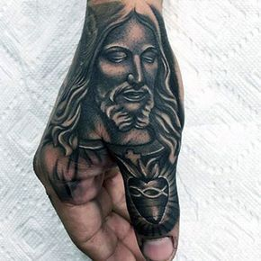 Tatuagem do rosto de Jesus na mão de um homem que termina em um coração sacro no dedão.
