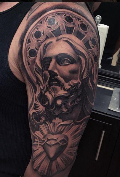 Tatuagem no braço de um homem do rosto de Jesus que parece uma escultura em mármore.