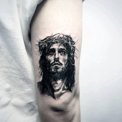 Tatuagem no braço de um homem com o rosto de Jesus em estilo realista.