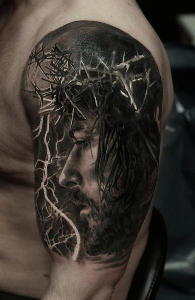 Tatuagem no braço de um homem com o rosto de Jesus visto de perfil usando uma coroa de espinhos.