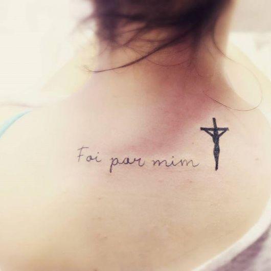 """Tatuagem de uma frase nas costas de uma mulher escrito """"Foi por mim"""" ao lado de uma cruz."""