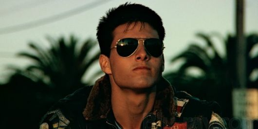 Tom Cruise no filme Top Gun olhando para o horizonte com um óculos aviador masculino de sol no rosto.