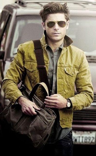 Zac Efron andando na rua. Ele está vestindo uma jaqueta aberta, camisa, calça jeans, relógio, uma bolsa lateral e óculos aviador escuros da Ray Ban.